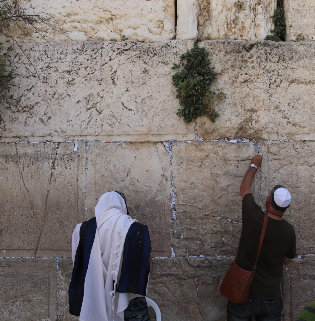 Prayers being inserted into cracks at the Western Wall