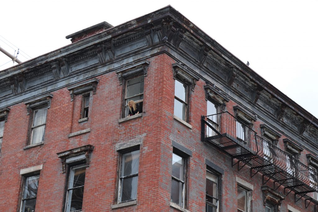 A local looking out of her window in Brooklyn. The building is classic New York architecture.
