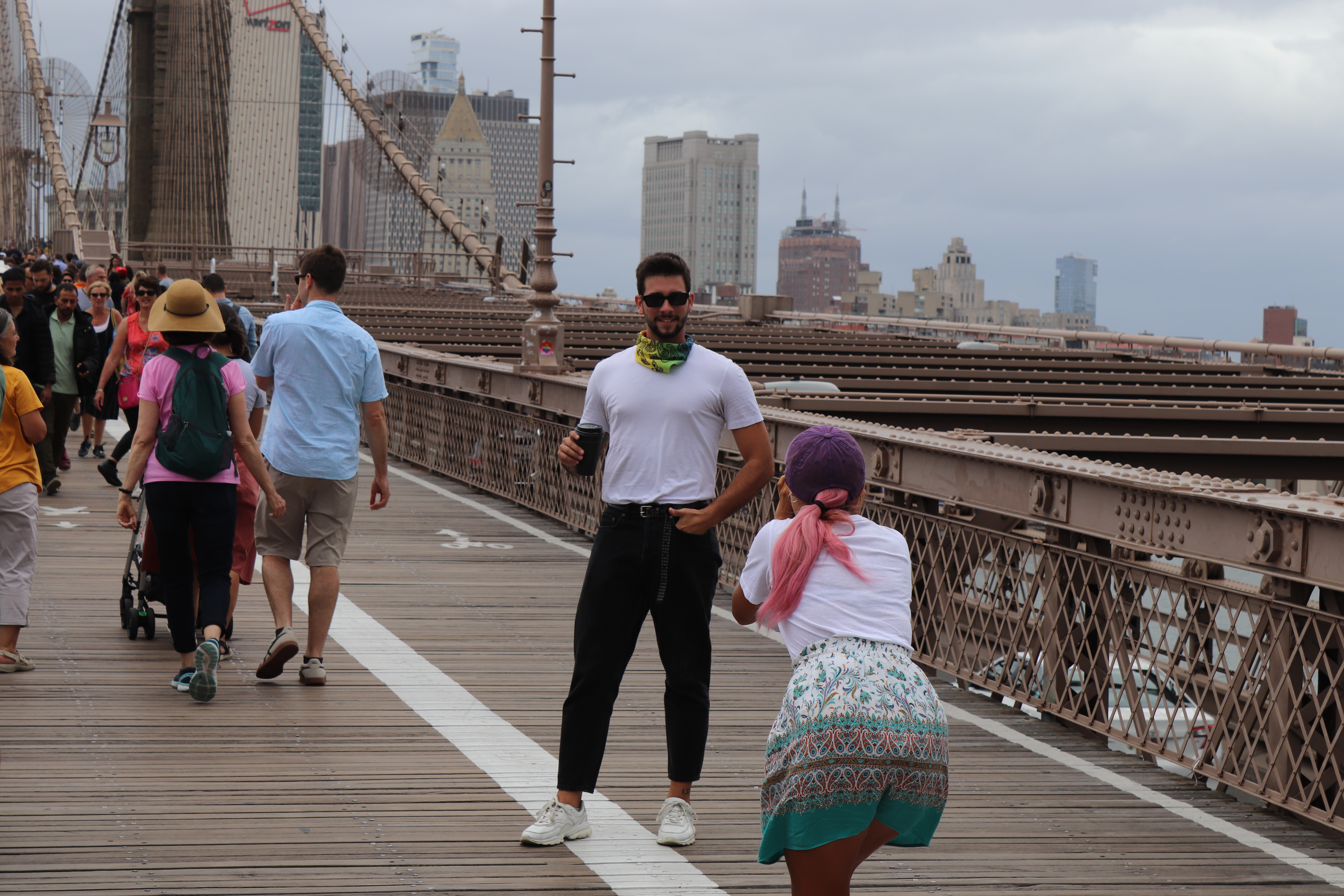 a visitor getting his photo taken on brooklyn bridge