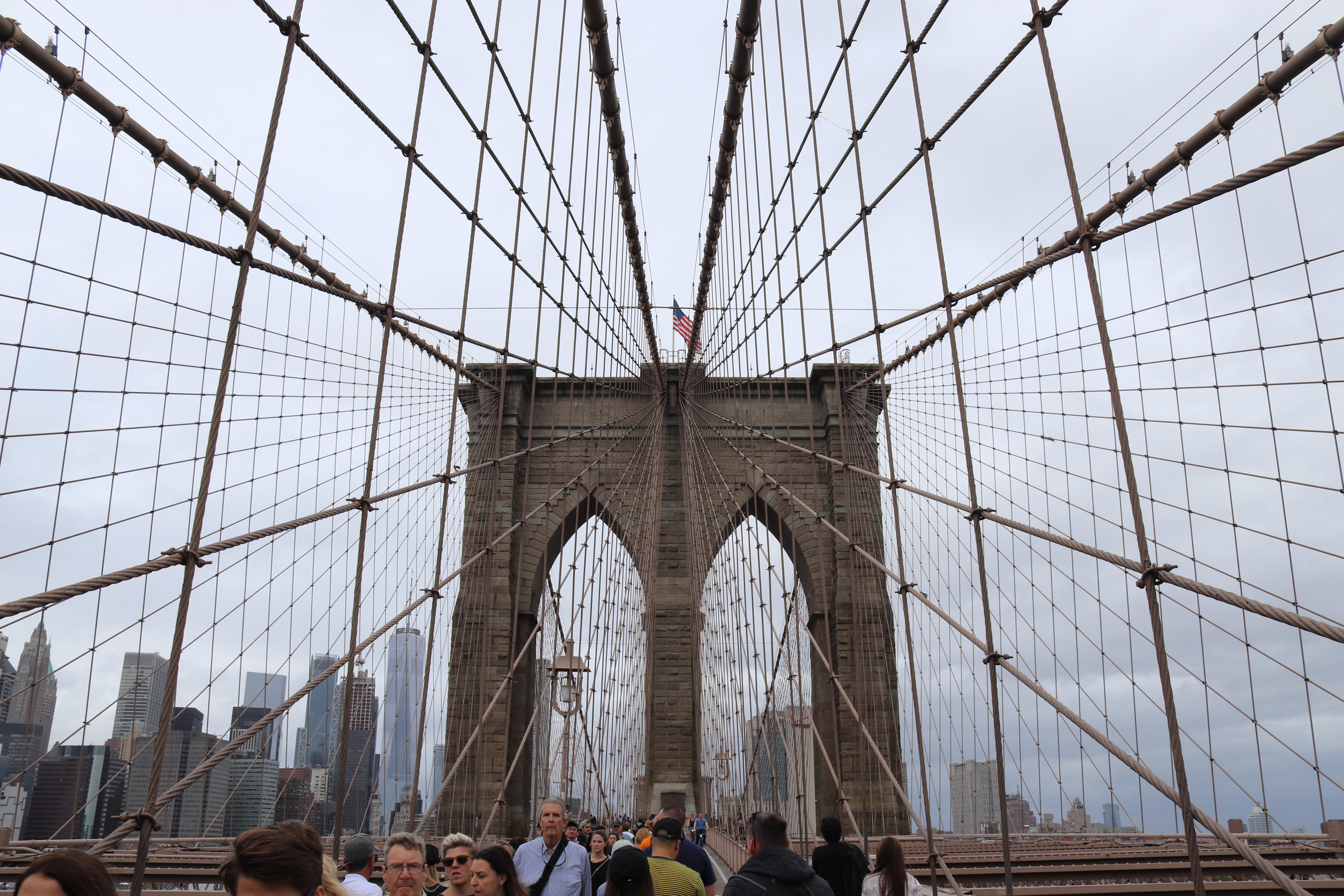 A view of Brooklyn Bridge's western pillar supported by iron suspension cables.