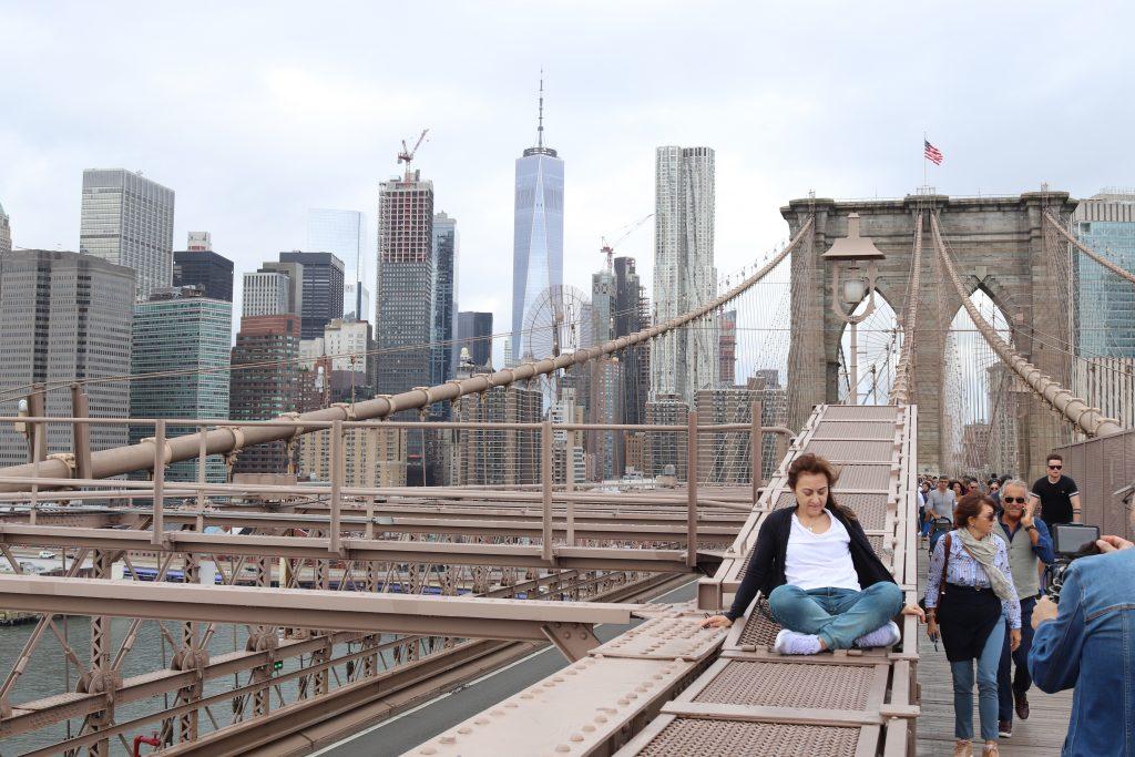 A tourist climbing onto a ledge for a photograph.
