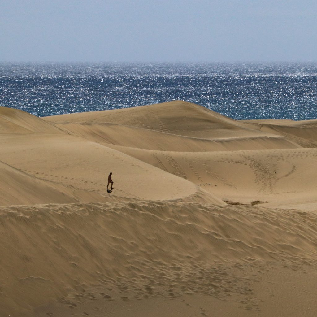 A man walks through the sand dunes of Maspalomas while the sea twinkles in the background.