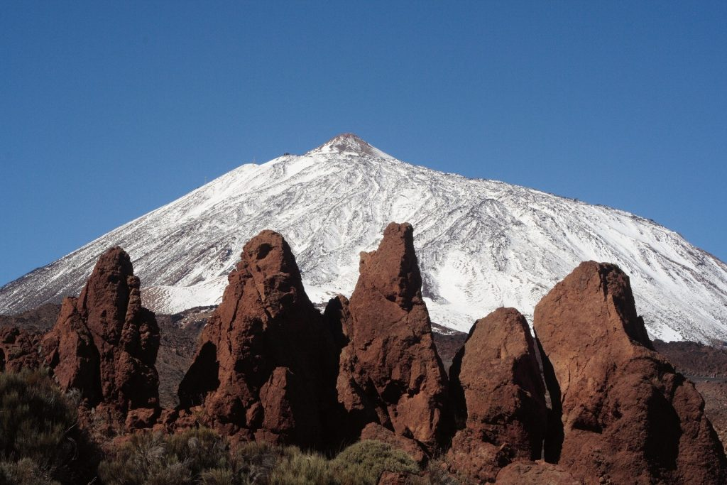 Mount Teide in the Snow. Volacnic rock formations in the foreground.