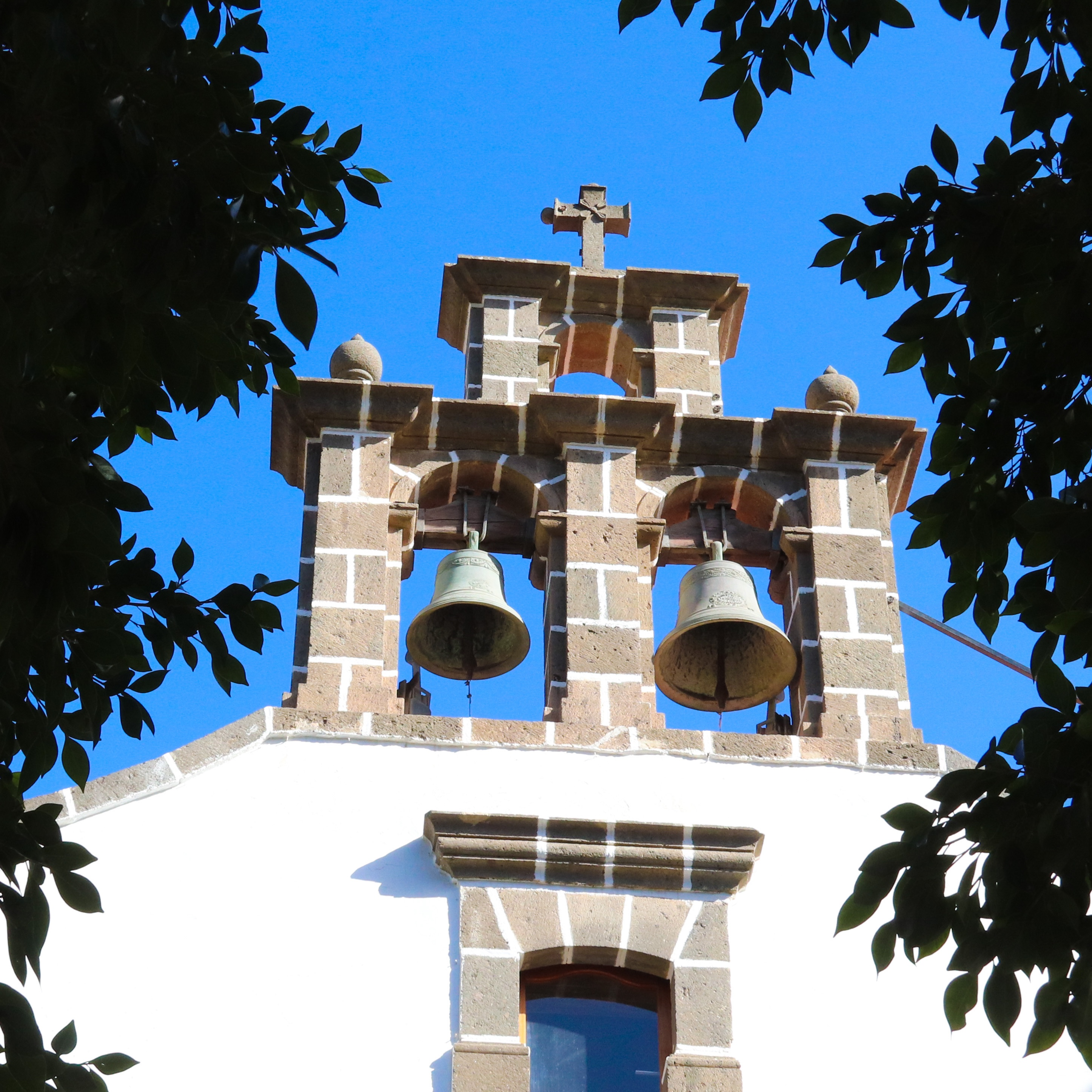 An open belfry of a the little white church in the village of Mogan in Gran Canaria.