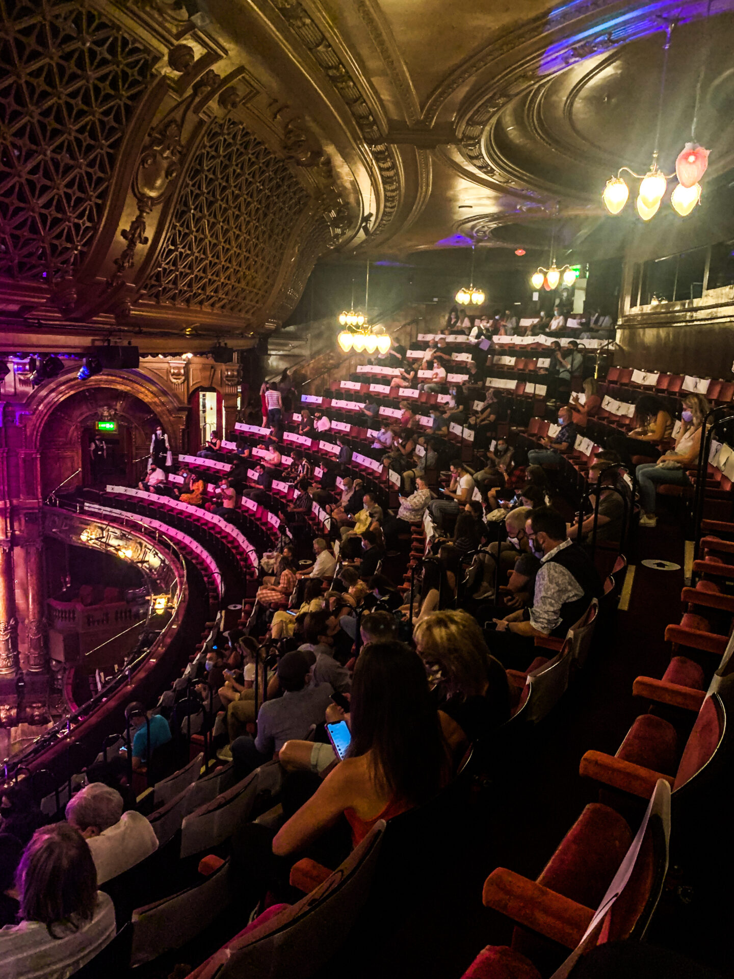 Social distancing inside the London Palladium. The white seats indicate that no one should sit there. There are spaces between each group of people.