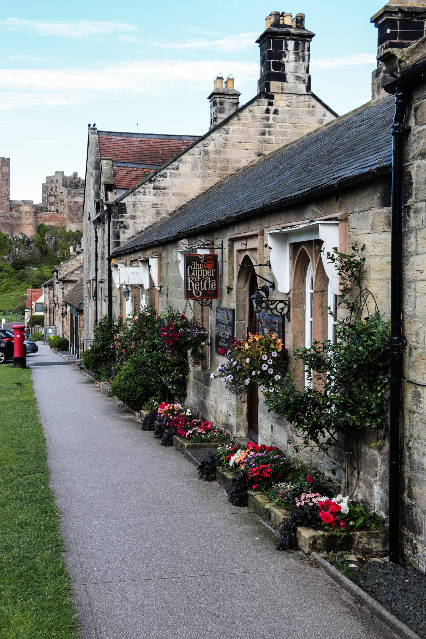 Picture perfect shops in Bamburgh Village - a cafe called the Copper Kettle with Bamburgh Castle in the background.