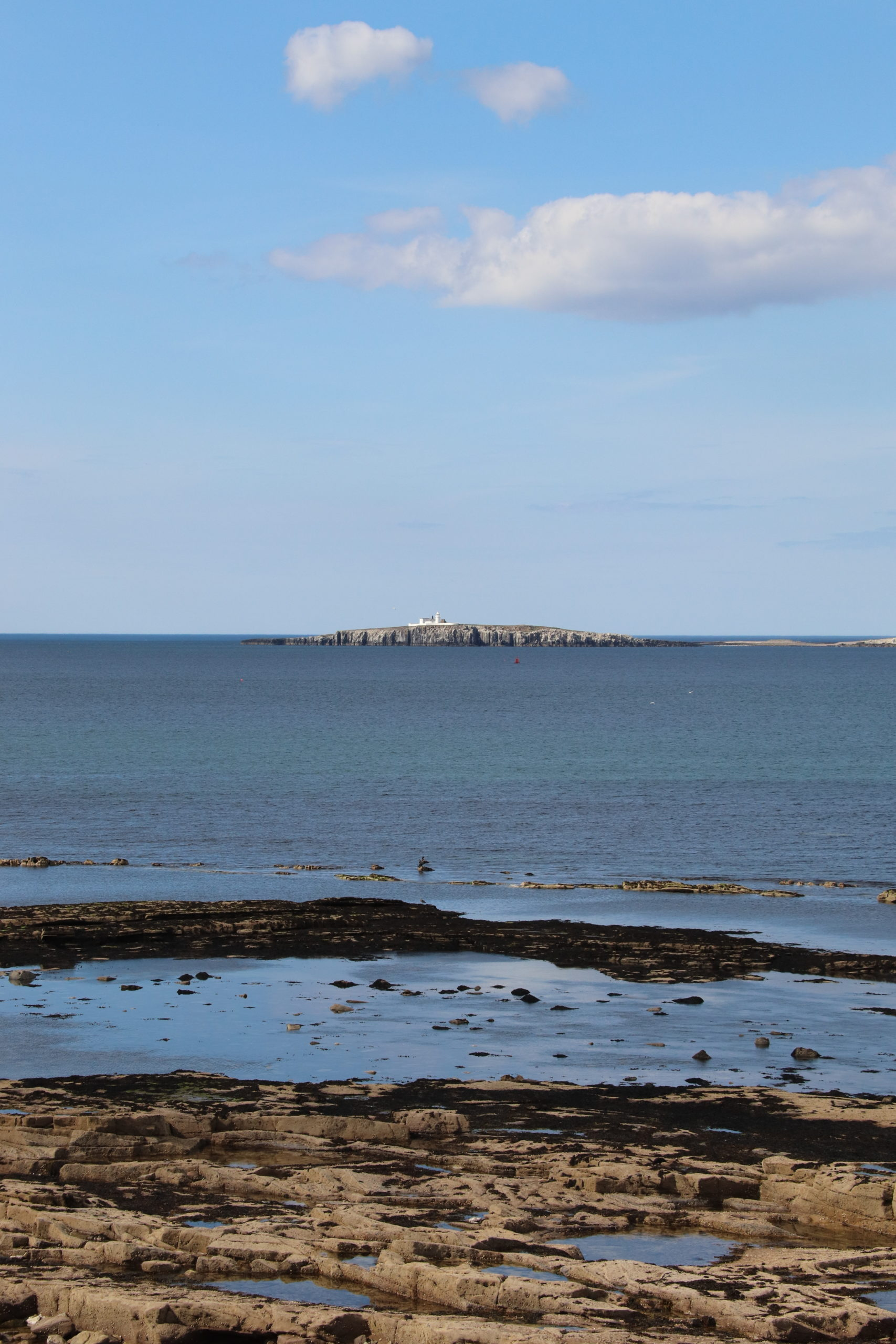 A view of the Farne Islands from Seahouses. There is a white building on the nearest island which is Inner Farne.