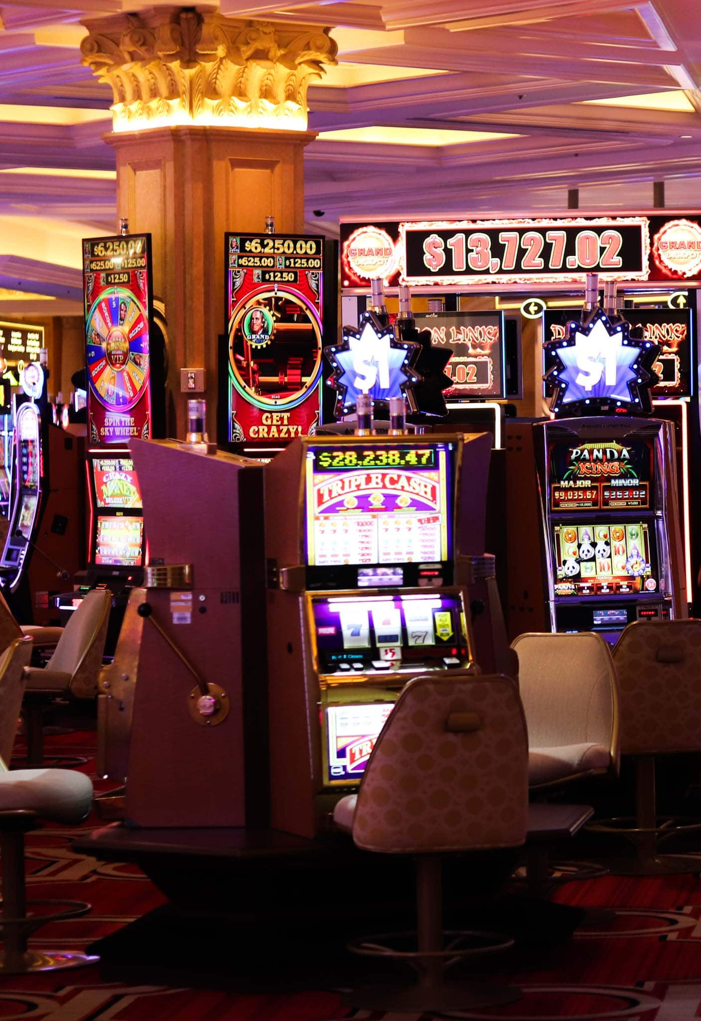 A view inside a Las Vegas casino with lots of neon lights and slot machines.