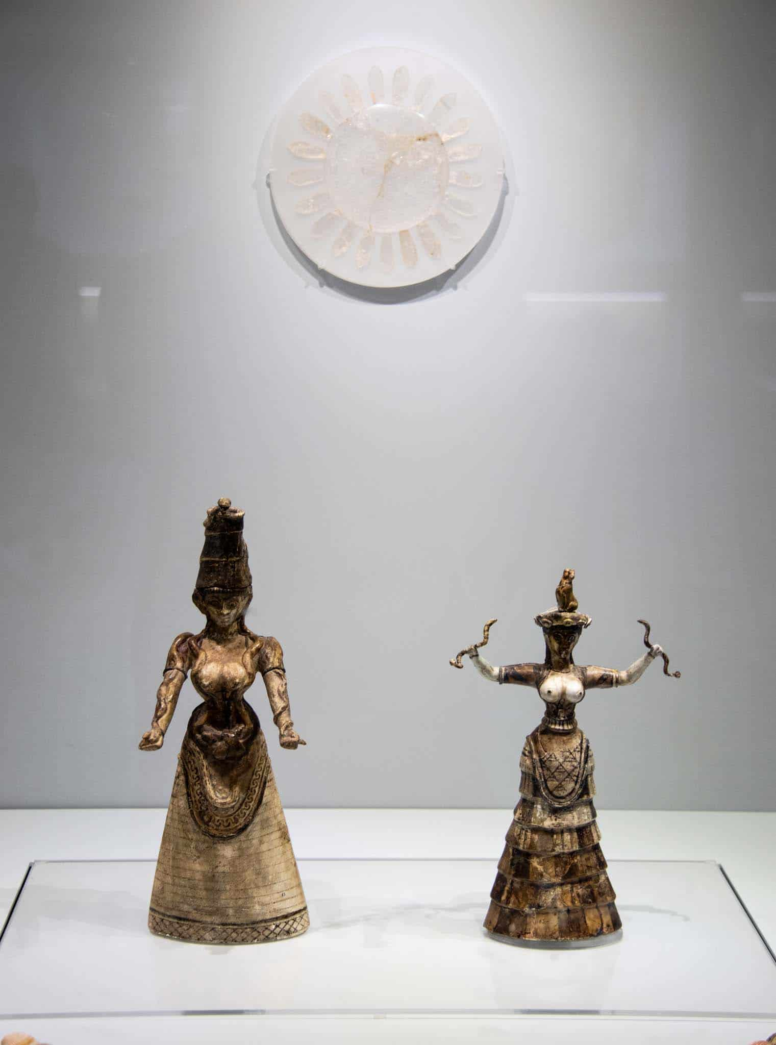 Minoan Snake Goddess and Priestess in the Heraklion Archaeological Museum. The snake goddess has snakes wrapped around her arms. The priestess holds a snake in each hand and has a Monkey on her head. Yes Louis - there's a monkey on her head!