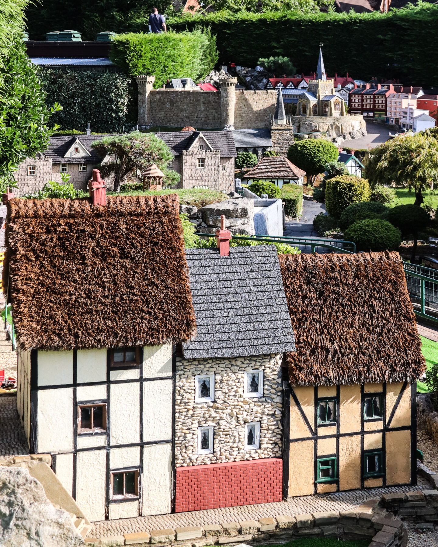 A view over Bekonscot, with thatched cottages in the foreground and church spires in the bakground.