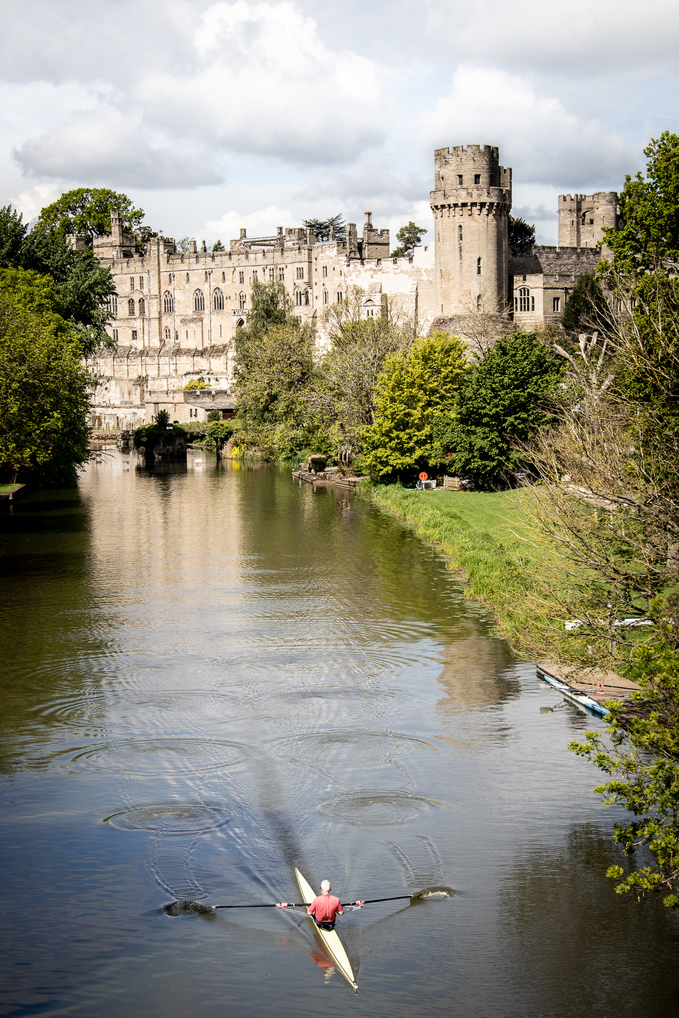 A view of Warwick Castle from Castle Bridge on the River Avon. A man is rowing down the River Avon and ripples show his path down the river.