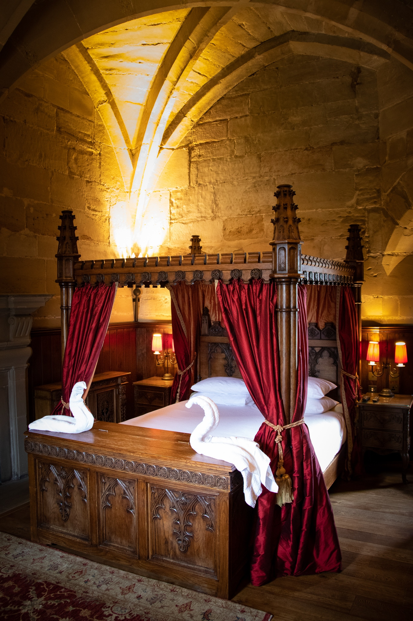A wooden 4 poster bed with red drapes inside the Tower Suites at Warwick Castle