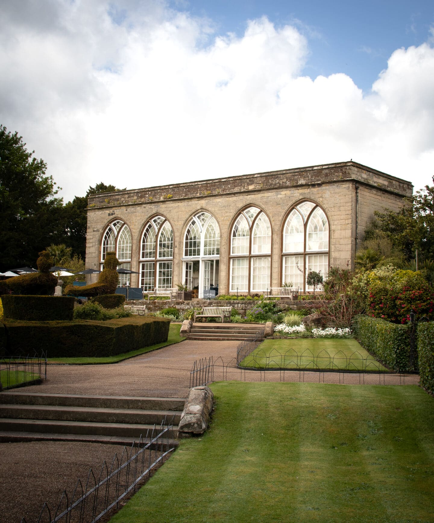 The conservatory is a square building with arched windows. The peacock gardens are in from of the conservatory with trimmed hedges and topiary birds.