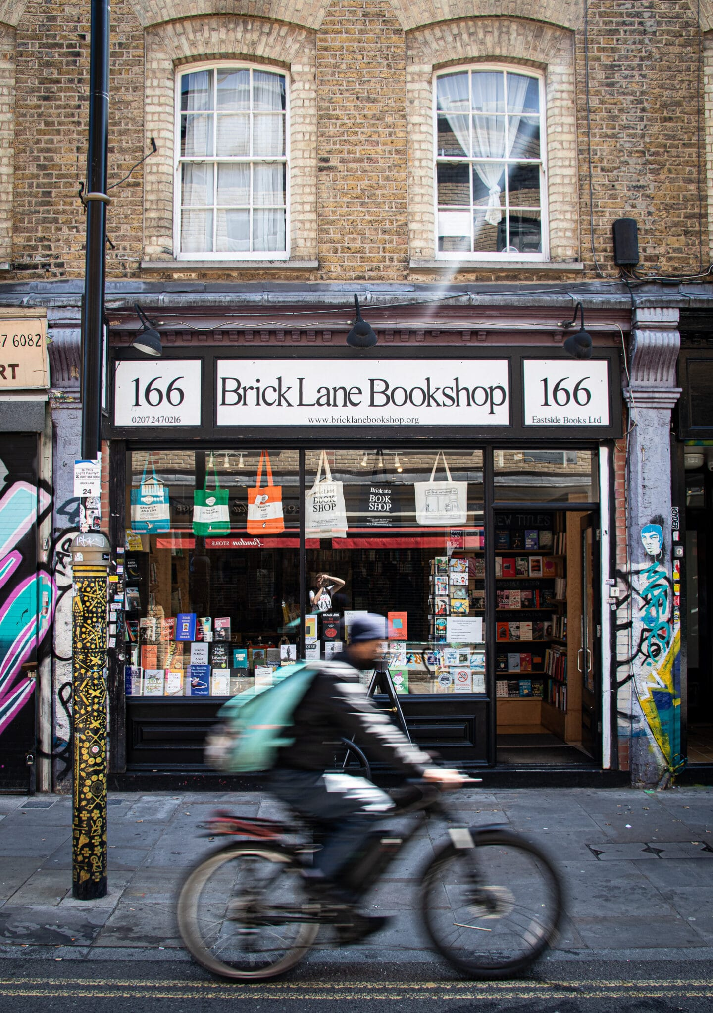 A cyclist cycles past the Brick Lane Bookshop which is at 166 Bricklane. The shops around Brick Lane are among my top recommendations of things to do in Shoreditch.